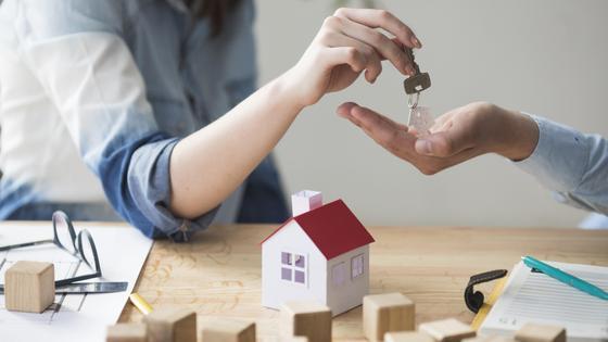 Менеджер банка отдает клиенту ключи от квартиры
