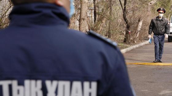 Полицейские ходят по двору оцепленной территории