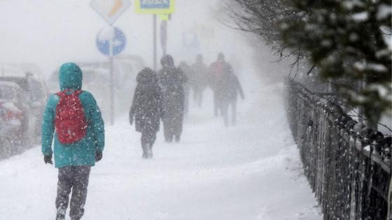 Люди гуляют по заснеженному тротуару в ветреную погоду