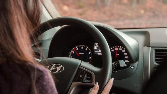 Женщина держит руль