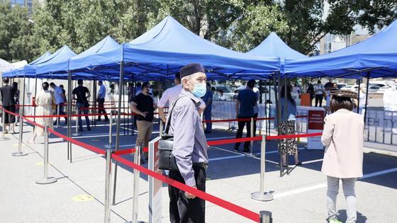 мужчина в маске стоит в очереди на тестирование