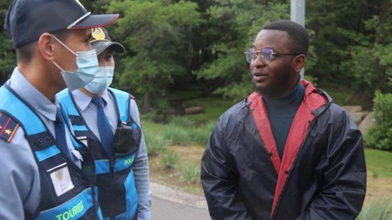 Полицейские разговаривают с нигерийцем