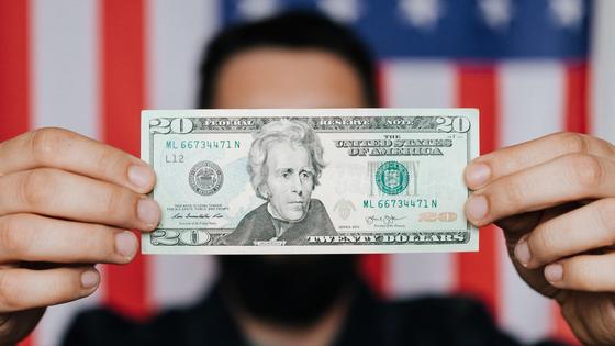 20-долларовая купюра на фоне флага США