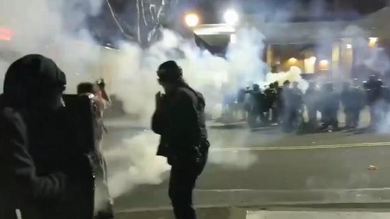 Две группы людей стоят друг напротив друга в дыму на улице