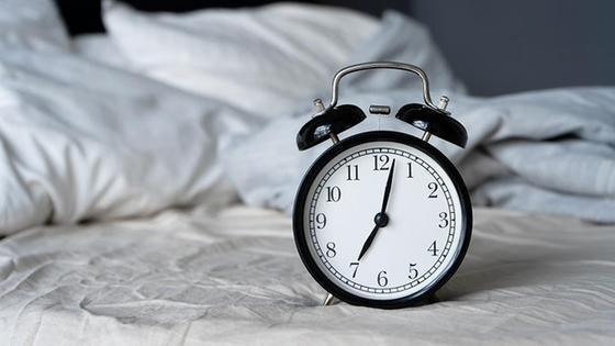Будильник на фоне белой постели