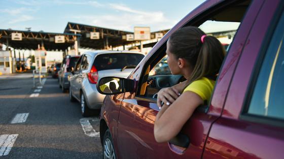 Девушка выглядывает из машины в очереди на прохождение таможенного поста