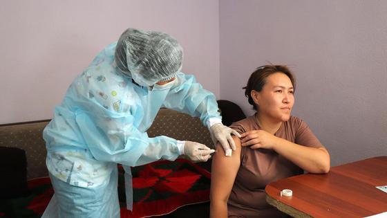 Женщине делают вакцину на дому