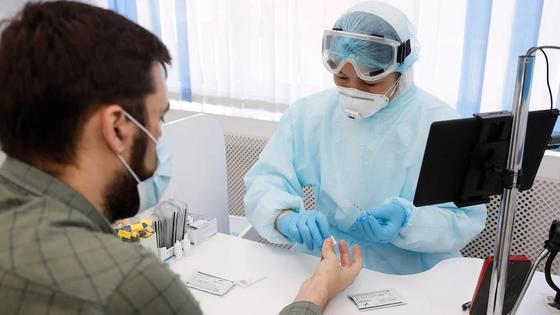 Медик берет кровь из пальца у мужчины