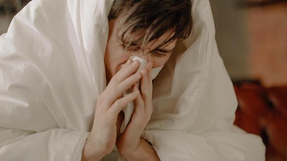 Мужчина вытирает нос салфеткой