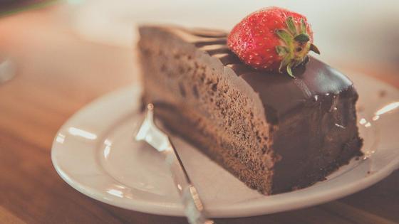 кусочек шоколадного торта с клубничкой на тарелке