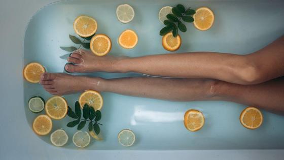 Женские ноги в ванной с кусочками цитрусовых