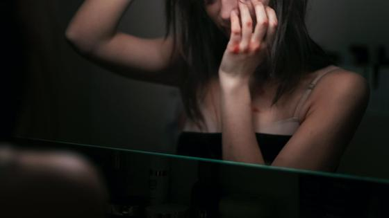 Девушка с синяками возле зеркала