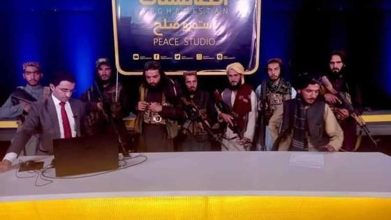 Журналист телевидения в окружении вооруженных талибов