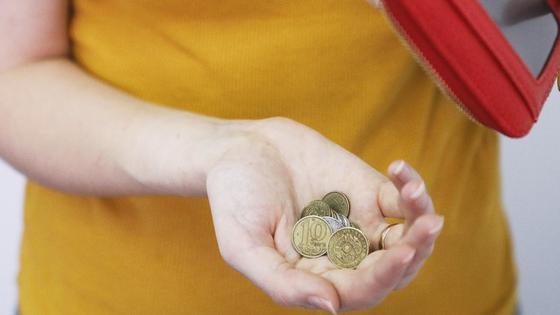 Женщина держит тенге в руке