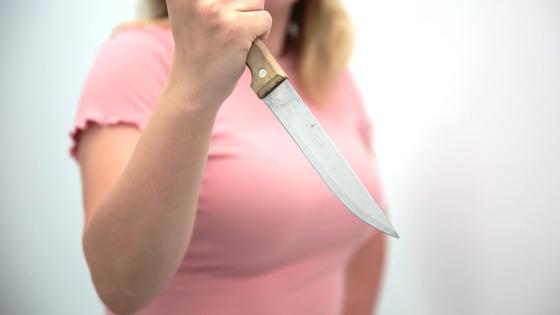 Девушка держит в руке нож