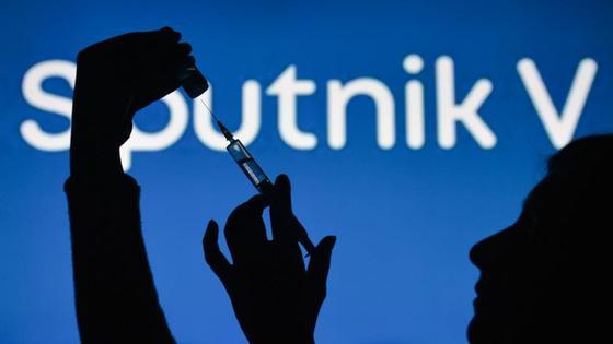 Женщина держит шприц с ампулой на фоне логотипа вакцины Sputnik V