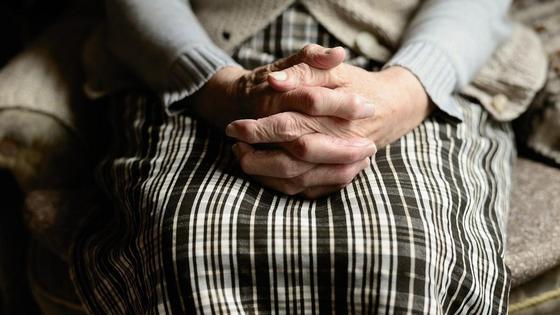 Морщинистые руки пожилого человека лежат на коленях
