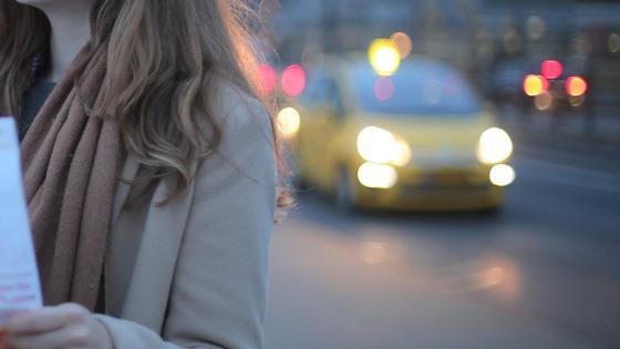 Девушка стоит на дороге спиной к такси