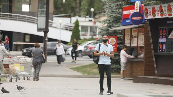 парень в маске стоит на улице