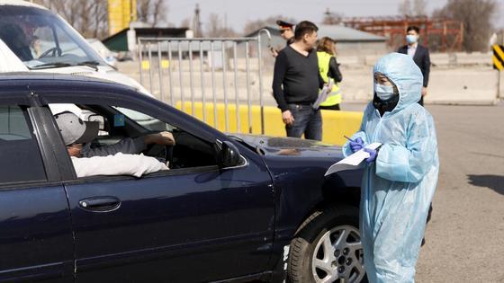 Девушка в костюме санитара подходит к машине