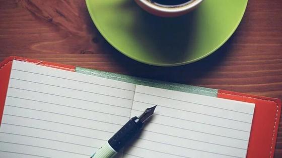 блокнот, ручка и чашка кофе