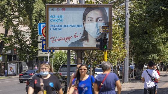 люди идут по улице в Алматы