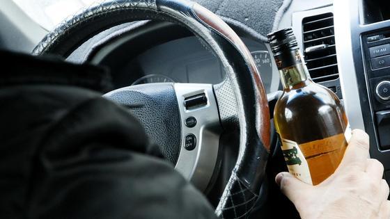 Мужчина сидит за рулем авто и держит бутылку