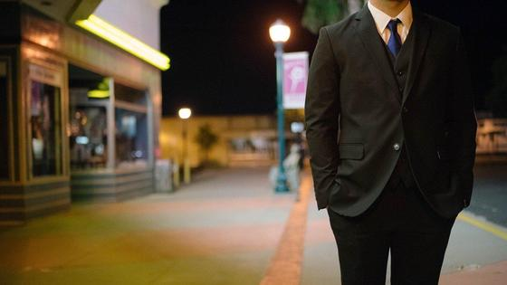 Мужчина в костюме стоит на улице