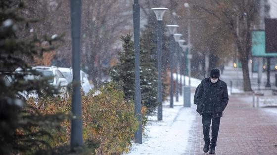 Мужчина в маске идет по улице