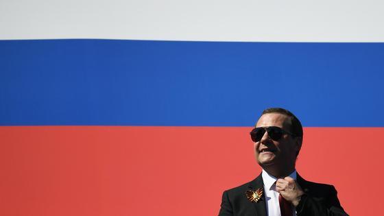 Дмитрий Медведев на фоне российского флага