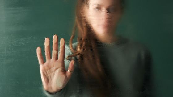 девушка прикасается к стеклу