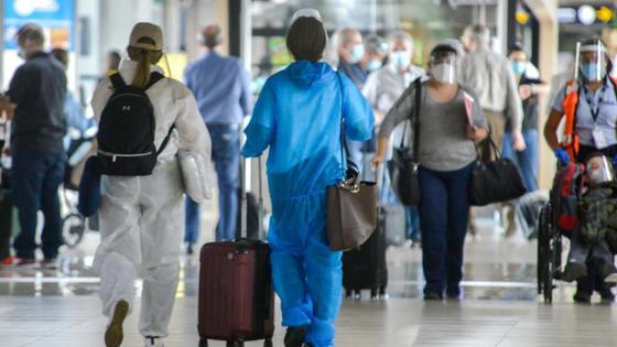 Авиапассажиры с багажом идут по холлу аэропорта