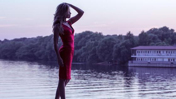 Девушка в красном платье на берегу водоема