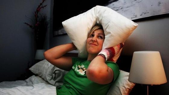девушка закрывает уши подушкой