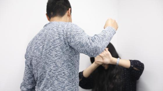 Мужчина заносит кулак над девушкой, пытающейся от него закрыться