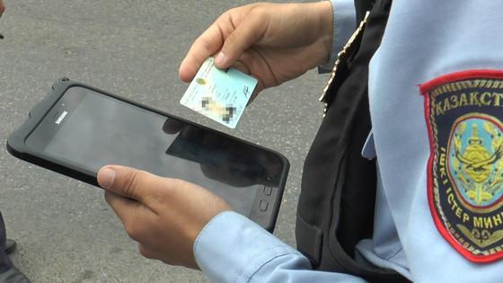 Полицейский проверяет удостоверение через планшет