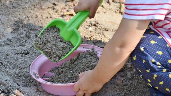 ребенок играется с песком