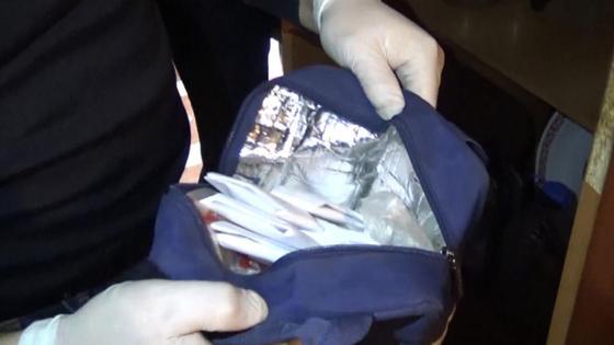 В руках у оперативника обнаруженные свертки с наркотиками