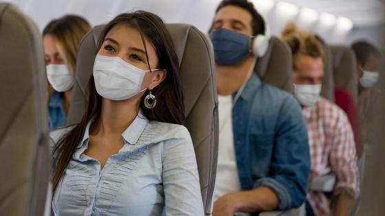 Пассажиры в масках сидят в креслах