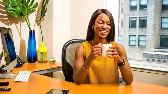 Женщина сидит за столом с чашкой кофе