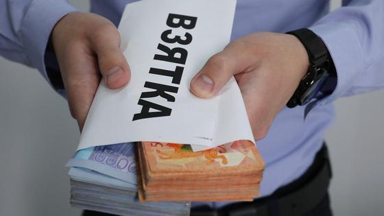 Мужчина протягивает конверт с деньгами