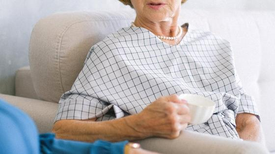 Пенсионерка сидит в кресле с чашкой чая