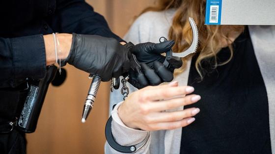 Полицейский застегивает наручники на руках женщины