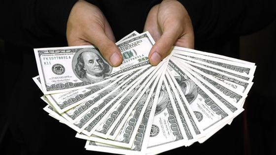 Мужчина держит доллары в руках