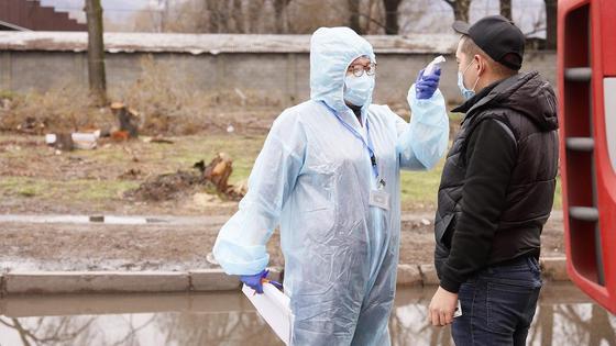 женщина в защитном костюме замеряет температуру