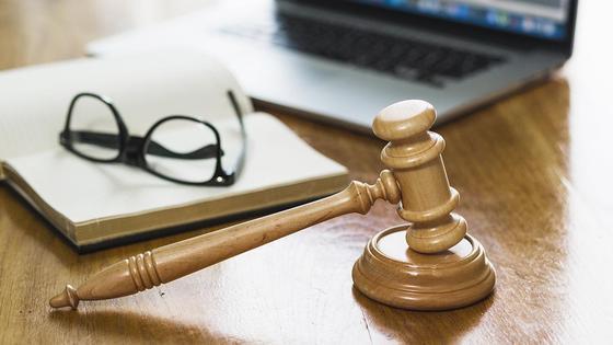 Молоток судьи, блокнот и ноутбук