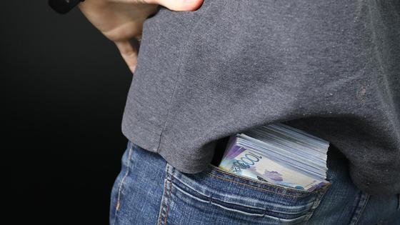 Пачка денег лежит у мужчины в заднем кармане