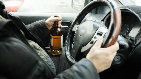 Водитель держит виски за рулем