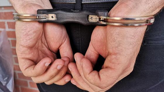 Мужчина стоит с руками, закованными за спиной в наручники