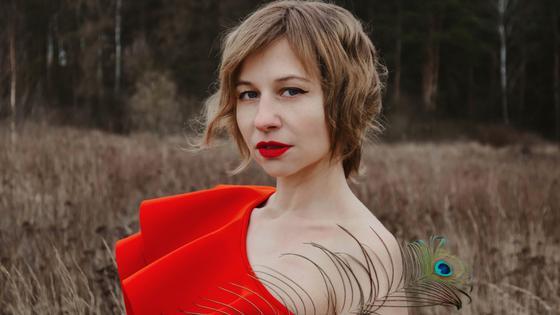 Девушка в красном платье с пером павлина